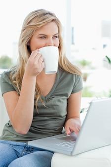 女性、彼女のラップトップを使用して飲み物を取って、側を見て