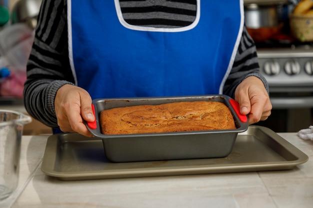 Женщина берет блин из духовки руками концепция домашней выпечки