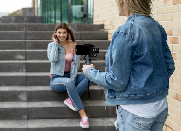 スマートフォンで友達の写真を撮る女性