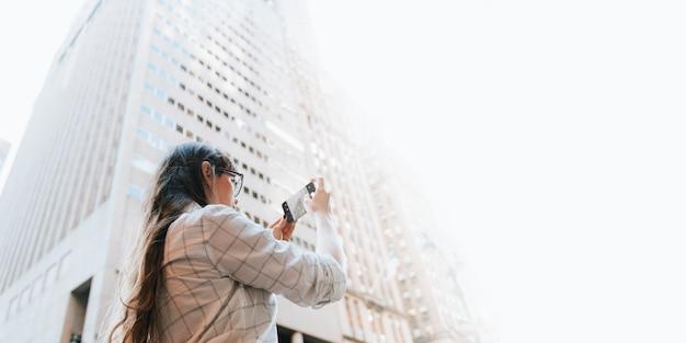 高層ビルの写真を撮る女性