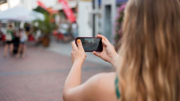Женщина, делающая фотографию с ее телефоном