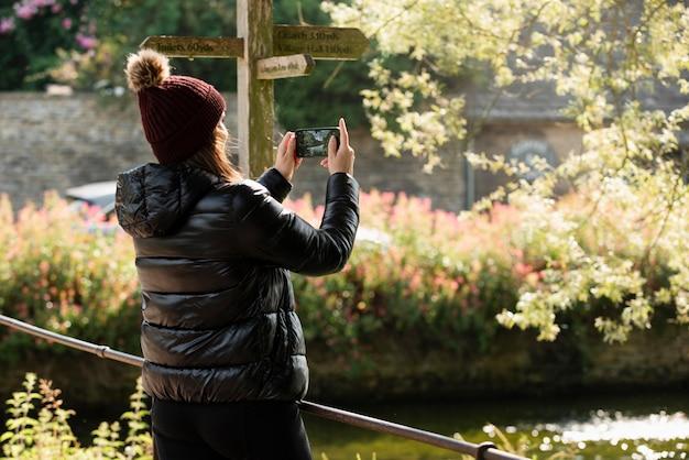 Женщина делает фото со своим смартфоном во время путешествия