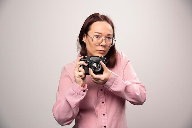 白のカメラで写真を撮る女性。高品質の写真