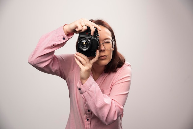 Женщина фотографирует с камерой на белом. фото высокого качества