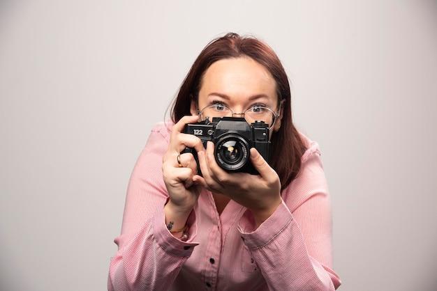 화이트 카메라로 사진을 찍는 여자. 고품질 사진