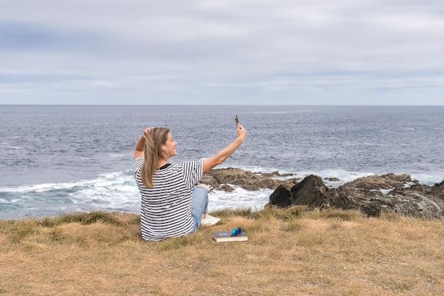 Женщина, делающая автопортрет с мобильным телефоном, сидя на берегу моря.