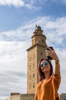 헤라클레스의 탑, 라 코루나, 스페인에서 셀카를 찍는 여성 - 탑에 초점
