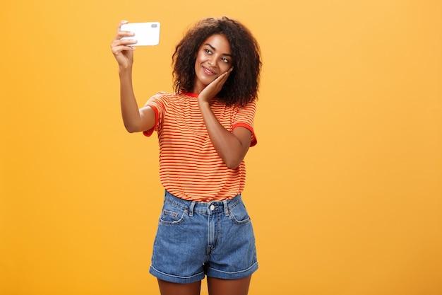 오렌지 벽 위에 부드럽게 웃는 손바닥에 셀카 기대어 머리를 복용하는 여자