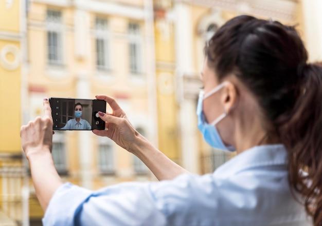 屋外でフェイスマスクを着用して自分撮りをしている女性