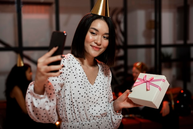 プレゼントと一緒に自分撮りをしている女性