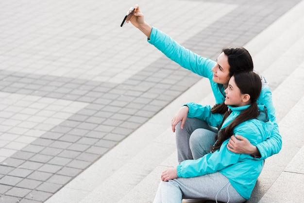 コピースペースを持つ娘と一緒に、selfieを取る女性