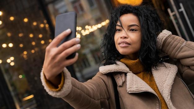 야외에서 그녀의 스마트 폰으로 selfie를 복용하는 여자