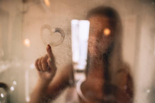 シャワーを浴びて、ガラスにハートを描く女性