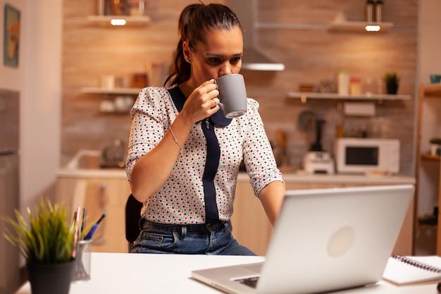 重要なプロジェクトのために自宅のキッチンでラップトップで夜遅くまで働いている間にコーヒーを一口飲む女性。深夜に最新のテクノロジーを使用して、仕事、ビジネス、忙しい、キャリアのために残業している従業員。