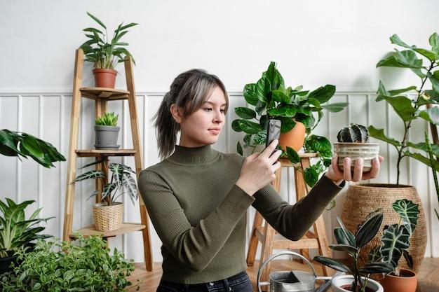 ソーシャルメディアのために自分の植物のスナップショットを撮る女性