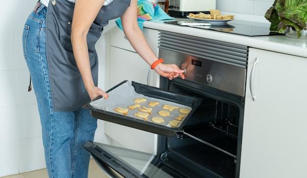 オーブンから焼きたてのクッキーのトレイを取り出している女性。家庭生活。
