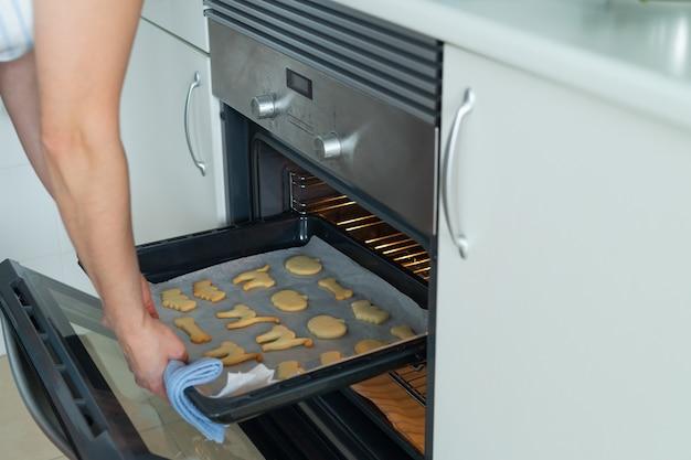 オーブンから焼きたてのハロウィーンのクッキーのトレイを取り出している女性家庭生活のコピースペース