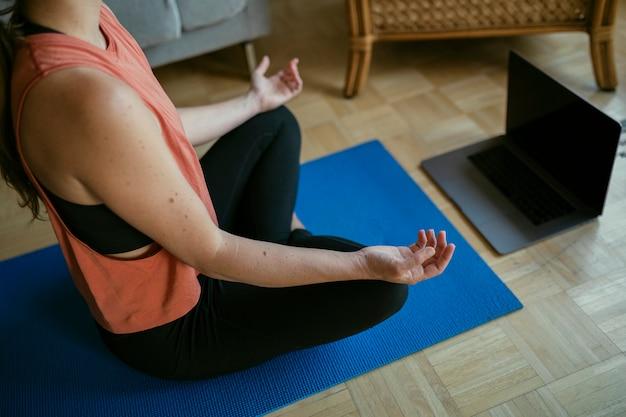 Женщина принимает онлайн-класс йоги во время карантина из-за коронавируса