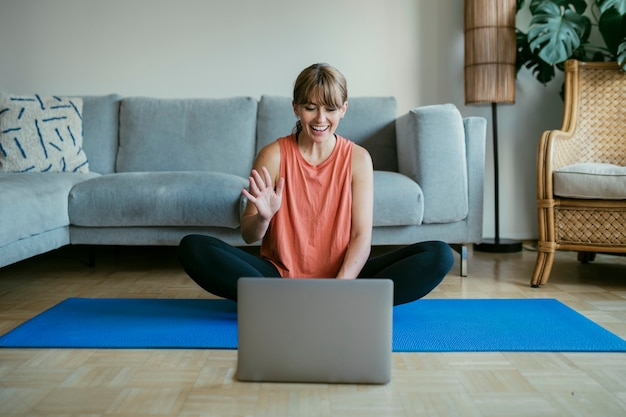 코로나바이러스 검역 기간 동안 온라인 요가 수업을 듣는 여성