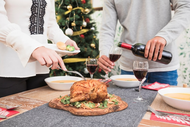 Woman taking baked chicken from christmas table