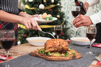 Woman taking baked chicken from festive table