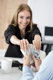 Женщина принимает партию стодолларовых купюр. продажность, взятка, понятие коррупции