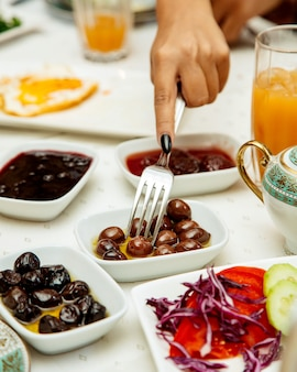 Woman taking black olive served for breakfast