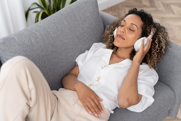 Woman taking a break while listening some music at home
