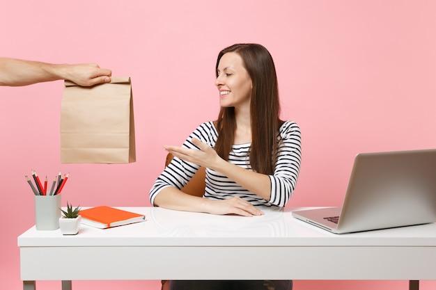 Женщина принимает коричневый ясный пустой пустой бумажный мешок ремесла, работу в офисе с компьтер-книжкой пк изолированной на розовой предпосылке. доставка продуктов курьерской службой из магазина или ресторана в офис. скопируйте пространство.