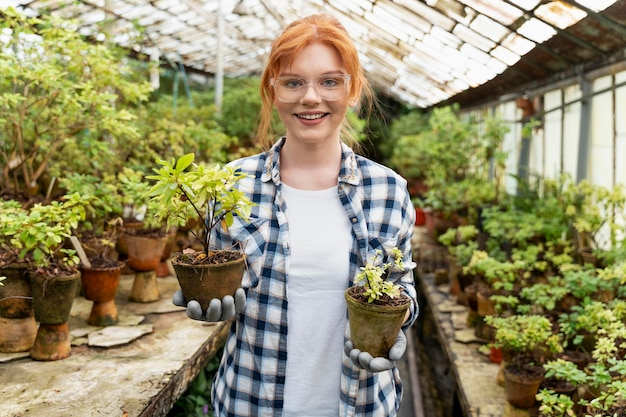 Woman taking care of her plants in a greenhouse