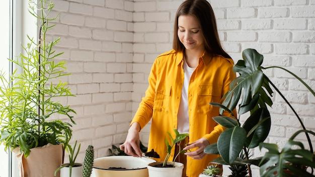 그녀의 집 정원에서 그녀의 식물을 돌보는 여자