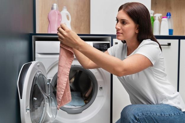 洗濯機から服を取っている女性