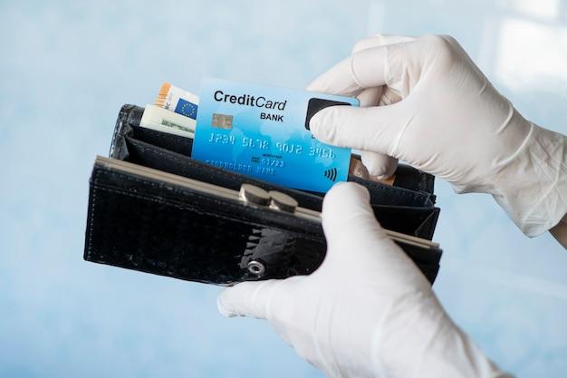 細菌やウイルスの拡散を防ぐためにゴム手袋を着用して女性の財布からクレジットカードを取り出す女性は、コロナウイルスのパンデミックの間に買い物をします。お金の微生物。現金の拒否。