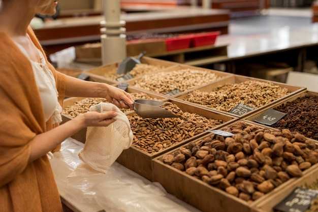 市場の場所で乾燥食品を取る女性