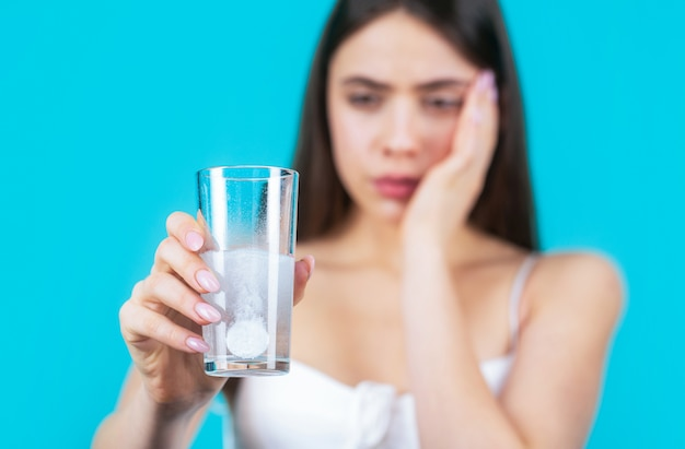 Woman taking drugs to releave headache. brunette take some pills, holds glass of water, isolated on blue.