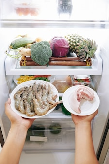 Woman taking food out of fridge
