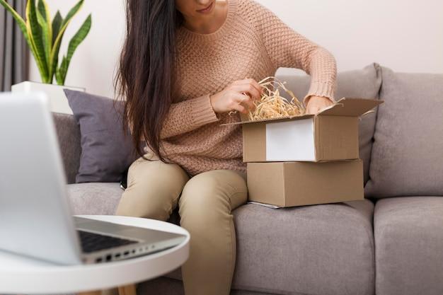 新しい購入品を箱から取っている女性