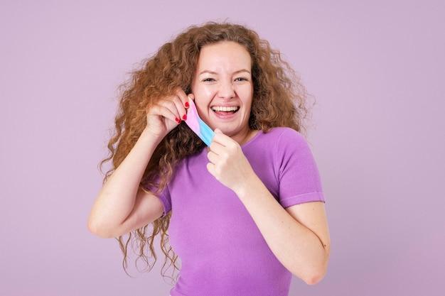 Женщина снимает маску с макета во время новой нормальной жизни