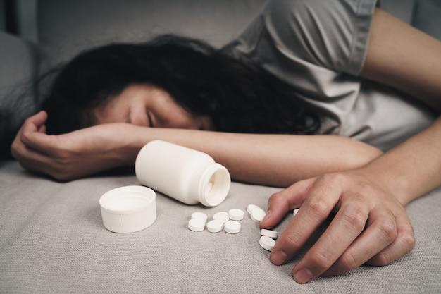 약을 과다 복용하고 열린 알약 병으로 소파에 누워있는 여자. 과다 복용 및 자살 개념입니다.