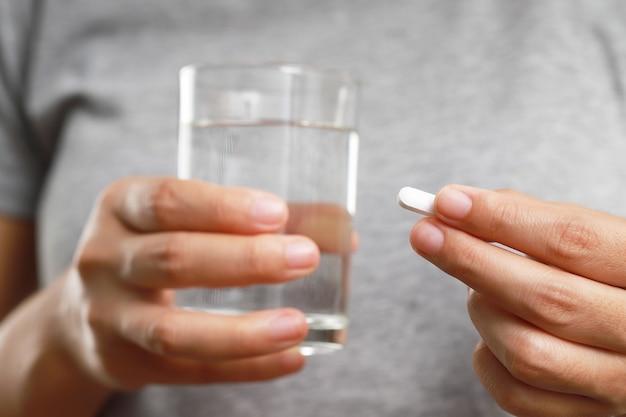 질병의 증상을 치료하기 위해 약을 복용하는 여성