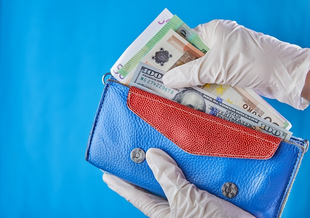 Woman taking money out of her wallet wearing rubber gloves to prevent the spread of bacterias or viruses or shopping during coronavirus pandemic.