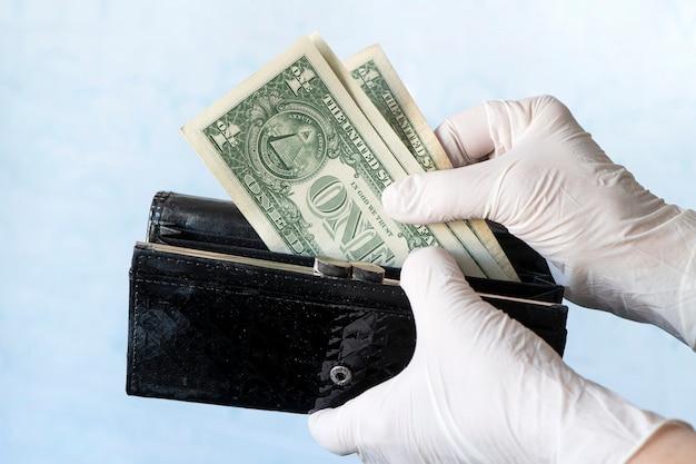 박테리아나 바이러스의 확산을 방지하기 위해 고무 장갑을 끼고 여성 지갑에서 돈을 꺼내는 여성은 코로나바이러스 전염병 동안 쇼핑을 합니다. 돈에 미생물. 현금 거부. 개념