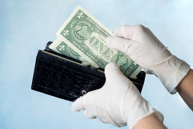박테리아나 바이러스의 확산을 방지하기 위해 고무 장갑을 끼고 여성 지갑에서 돈을 꺼내는 여성은 코로나바이러스 전염병 동안 쇼핑을 합니다. 돈에 미생물. 현금 거부.