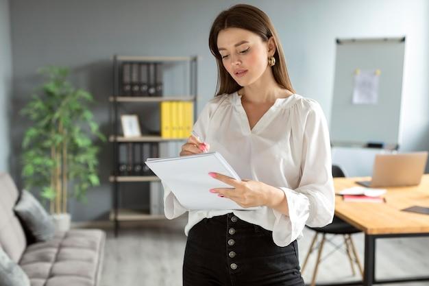 Женщина делает заметки на своем ноутбуке на работе