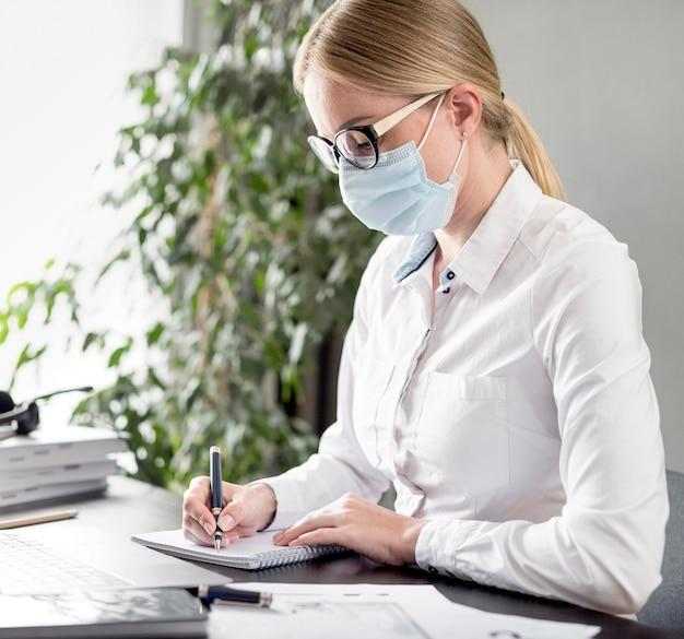 フェイスマスクを着用しながらメモを取る女性