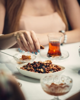 Woman taking nuts from white plate.