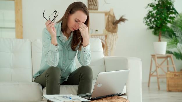 Женщина снимает очки, устала от работы с ноутбуком, проблема после длительного использования ноутбука