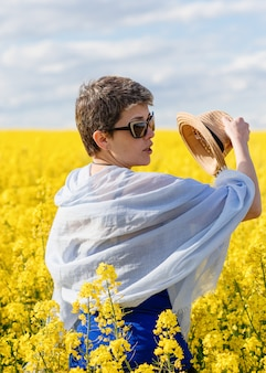 Woman taking off her hat in yellow rapeseed field on warm sunny spring day
