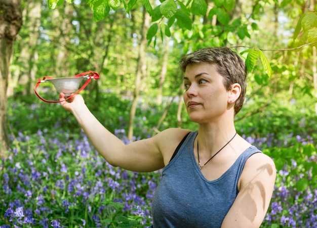 Woman  taking off her mask and sitting on meadow between bluebells in forest