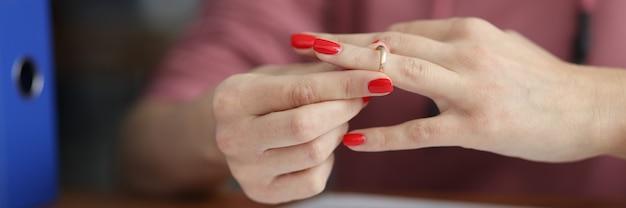 ドキュメントのクローズアップの前で彼女の指から彼女の結婚指輪を脱いでいる女性